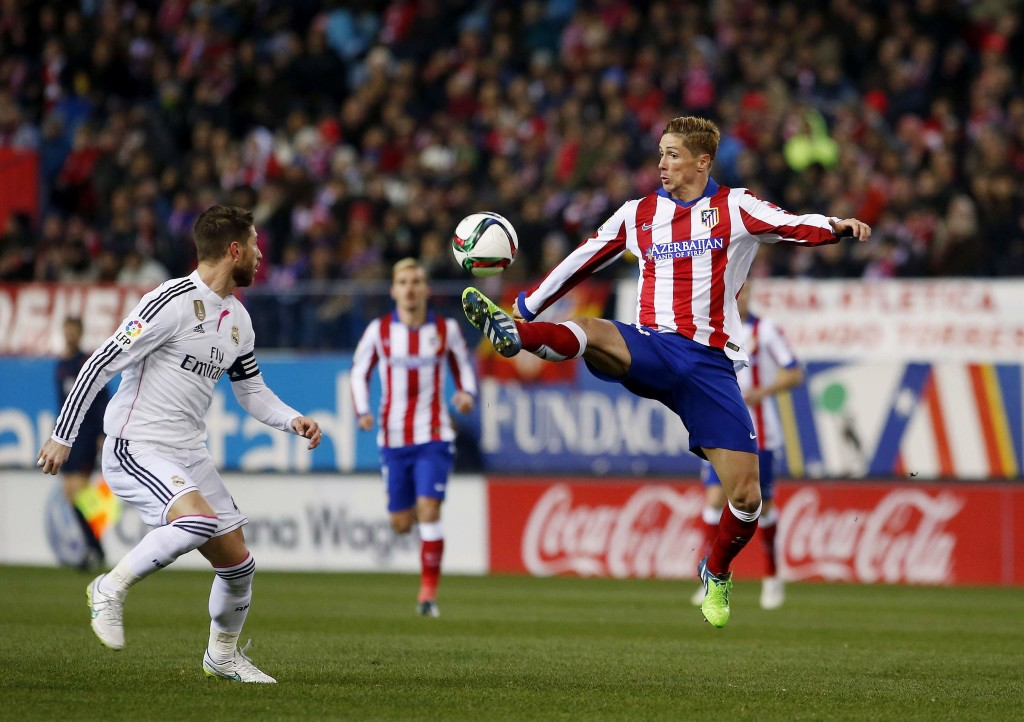 Atletico Madrid's Torres controls the ball past Real Madrid's Ramos during their Spanish King's Cup soccer match at Vicente Calderon stadium in Madrid